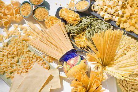 Italian raw pasta messed up: spaghetti, tagliatelle, macaroni, fettuccine, ribbons, lasagna, orecchiette, conchiglie, tubes, etc....