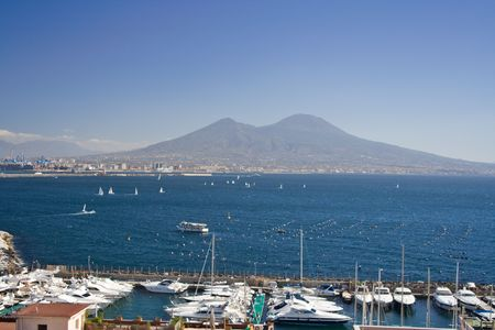 View of Mount Vesuvius from Naples. View of th e touristic marina and the gulf of Naples with boats sailing.