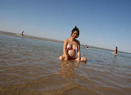 Beauty asian pregnant girl sit in water, bikini