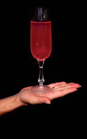 Wine on a women hand on black background photo