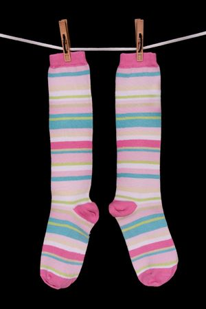 Striped socks, cord, clothespin, black background Stock Photo