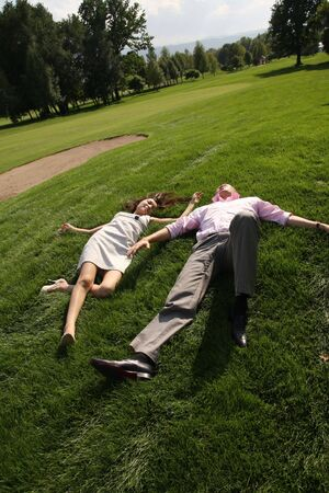 To fall in love, men and woman lying on green grass photo