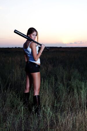 The bad girl costs with a baseball bat, in a grass photo