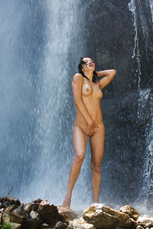 Nude european woman posing in waterfall, nature