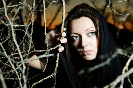 East beauty with green eyes in a black scarf on a decline makes the way through trees photo