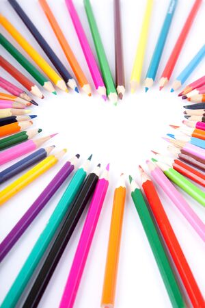 Colour pencils laid out in the form of heart photo