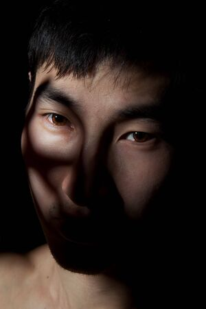 The obverse portrait of the young Asian man which poses a mug Stock Photo - 6596330