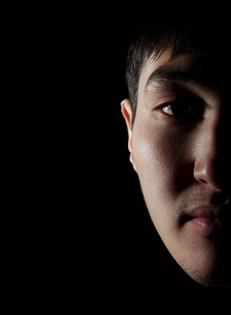 Portrait of the young Asian guy on which it is represented a half of the face Stock Photo - 6611835