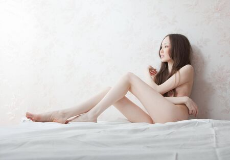 The bared girl the Asian lies on the bed having leant the elbows to a wall Stock Photo