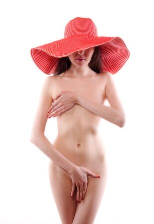 The bared Asian girl in a red hat having covered with hands poses on a white background