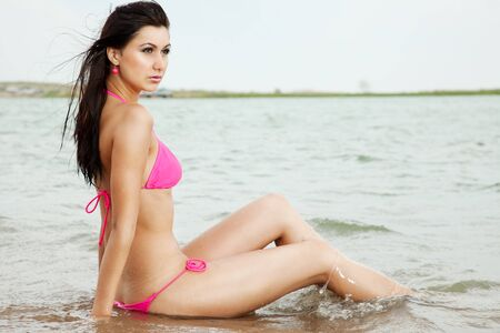 The girl in a pink bathing suit and sun glasses poses sitting in water photo