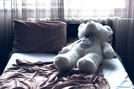 On the straightened bed the teddy bear lies Stock Photo