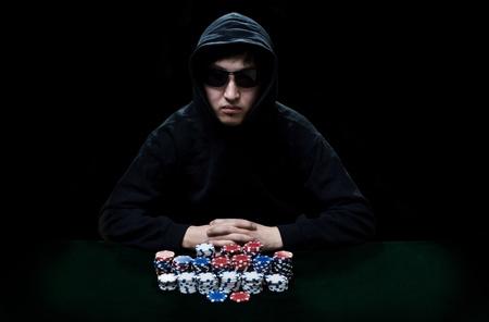 texas hold em: El chico de gafas oscuras, el jugador en gamblings se sienta en una mesa antes de que los chips un p�ker de mont�n Foto de archivo