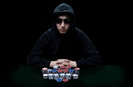 The guy in dark glasses, the player in gamblings sits at a table before it a heap poker chips