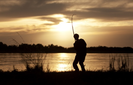The silhouette of the guy with a fishing tackle, at sunset, which fishes   Stock Photo
