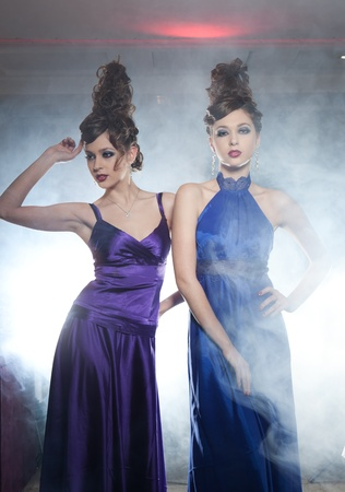 Two glamour girls the twins, one in a dark blue dress another in the violet pose in a smoke photo
