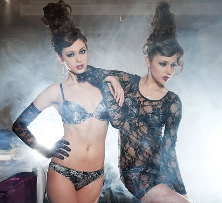 Two glamour girls twins, in underwear, pose in a smoke photo