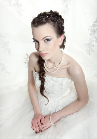 hairdress: Very beautiful girl the bride, with the imposed make-up and a hairdress