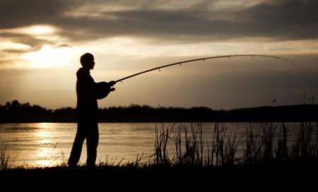 hengelsport: Het silhouet van de man met een vissersboot aan te pakken, bij zonsondergang, die vissen