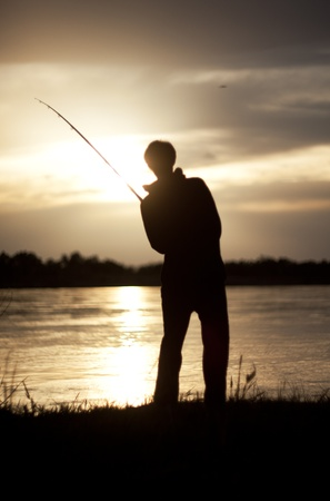 The silhouette of the guy with a fishing tackle, at sunset, which fishes