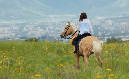 The girl skips on a green field on the horse