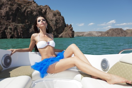 The beautiful girl sits on a sofa in a back part of a boat and poses on the sun Stock Photo