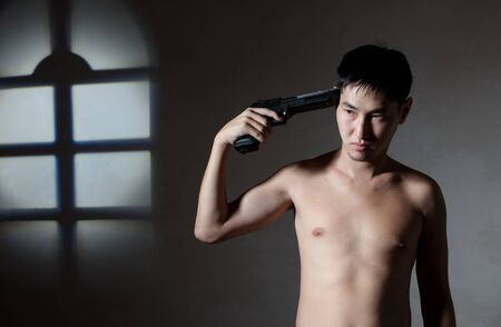 The guy with a pistol aims to itself in a temple Stock Photo - 12941879