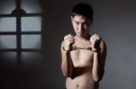 The concluded guy of the Asian appearance in handcuffs Stock Photo - 12941782