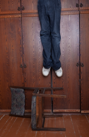 The suicide hung up at a wall case under which the chair lies Stock Photo