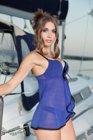 The beautiful girl with fine forms poses about the white yacht photo