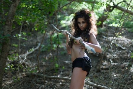 The beautiful girl amazon poses in jungle with a spear photo