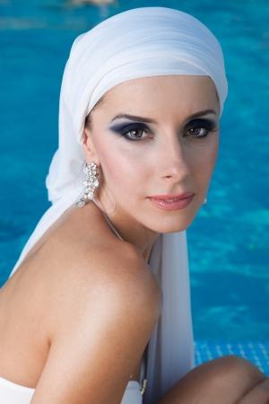 Güzel doğu kız beyaz bir eşarp havuz eşiğinde bir mayoyla oturur