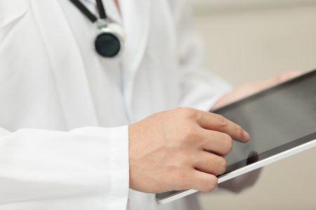 Doktor bir tablet bilgisayar, boynuna asılı bir stetoskop ile çalışan Stock Photo
