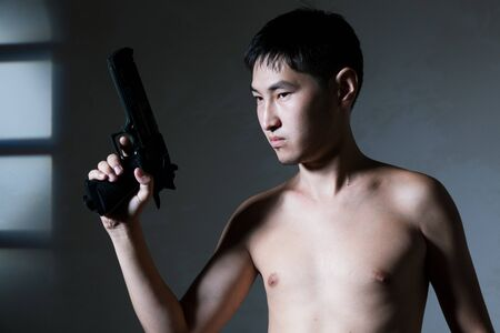 The guy of the Asian appearance bared on a belt aims a pistol Stock Photo - 16334726
