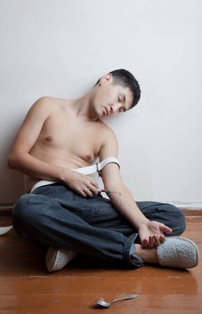 túladagolás: A fiatalember a drogfüggő fekszik a padlón tudat nélkül a túladagolás Stock fotó