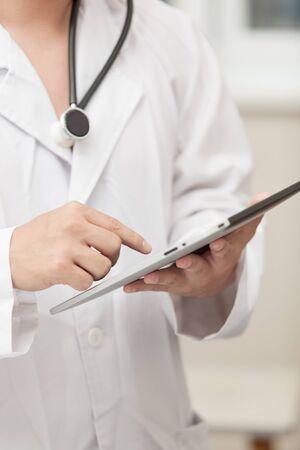 hanging around: M�dico que trabaja con un equipo Tablet PC, un estetoscopio colgando alrededor de su cuello