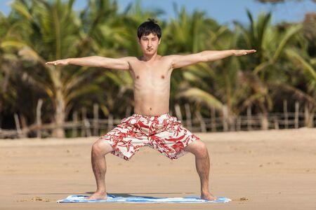 The guy of Asian appearance practices yoga on a beach against palm trees photo