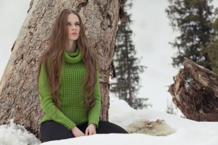 Girl in green in the mountains in winter, standing, sitting at stump Stock Photo
