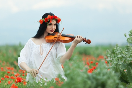 A girl with a violin in a white shirt on a poppy field