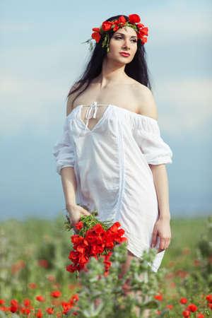 Başında bir çelenk giyen alanında bir buket çiçek ile kız
