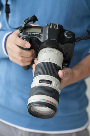 tele: Photo camera with tele lens in male hands, close-up Stock Photo