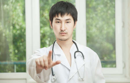 Instructed by the doctor, a guy in a white coat points a finger in the office Banco de Imagens
