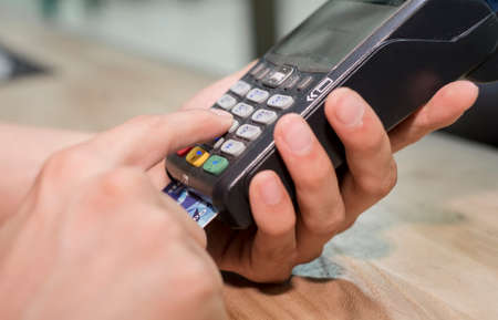 carry out: Mans hands carry out payment according to the card by means of the terminal