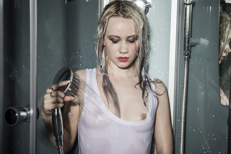 The seminude girl poses in a shower booth