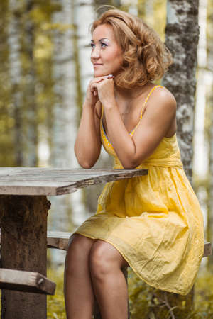 A girl in a yellow dress sitting in the woods behind a wooden table