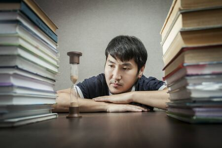 The young man looks at hourglasses lying on a table between textbooks photo