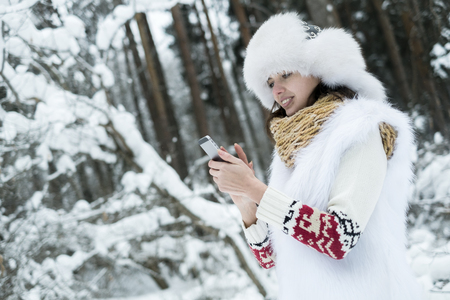 The girl in mittens and a woolen jacket in the wood use a smartphone