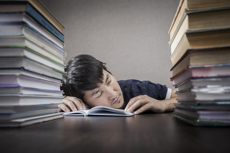 The young man sleep on a table between textbooks photo