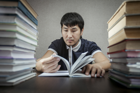 The young man looks at book on a table between textbooks photo