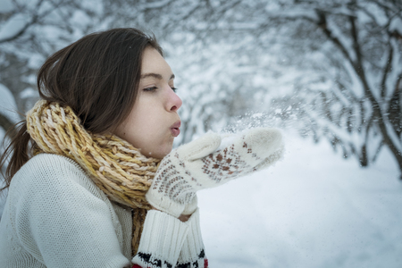 The girl is warmly dressed, blows off snow from hands